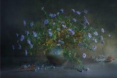 与一朵大花束小蓝色花的静物画在疏散的泥罐和很多玻璃透明小瓶的分支 库存图片