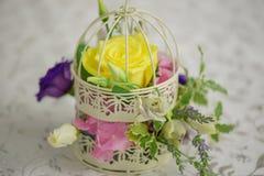 与一朵大黄色玫瑰的混杂的花的布置在葡萄酒装饰鸟笼作为婚礼桌焦点 库存照片