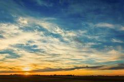 与一朵巨大的蓝天和白色云彩的水多的橙色日落 图库摄影