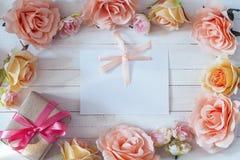 与一朵桃红色丝带、礼物盒和玫瑰色花o的白色空插件 免版税库存照片