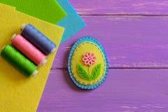 与一朵桃红色花的小毛毡复活节彩蛋装饰,色的螺纹集合,平的毛毡在紫色木背景覆盖 免版税库存照片