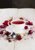 与一朵玫瑰的果子茶在一个白色杯子 免版税库存图片