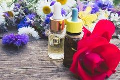 与一朵玫瑰的精油在野花附近的一个玻璃瓶在木背景 图库摄影