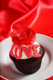 与一朵红色玫瑰的杯形蛋糕在配件箱的顶层和礼品在红色缎b 免版税库存图片