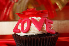 与一朵红色玫瑰的杯形蛋糕在配件箱的顶层和礼品在红色缎b 免版税库存照片