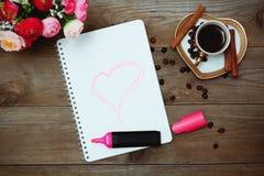 与一朵被绘的心脏、咖啡和花的笔记薄 库存照片