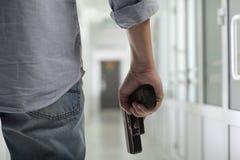 与一杆枪的凶手在走廊 免版税库存图片
