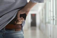 与一杆枪的凶手在走廊 库存照片