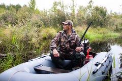 与一杆枪的猎人在小船 免版税库存照片