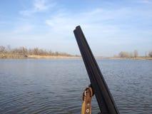 与一杆枪的猎人在湖 免版税库存图片