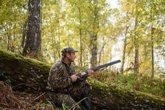 与一杆枪的猎人在秋天森林 免版税库存照片