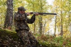 与一杆枪的猎人在秋天森林 免版税图库摄影