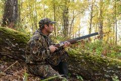 与一杆枪的猎人在秋天森林 库存图片