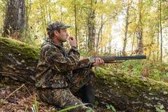 与一杆枪的猎人在秋天森林 免版税库存图片