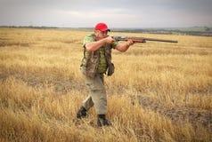 与一杆枪的猎人在领域 免版税库存图片