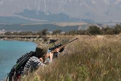 与一杆步枪的猎人在河岸 库存照片