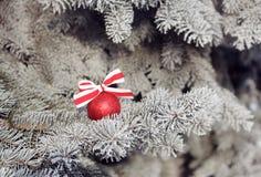 与一条丝带的发光的圣诞节球在一棵积雪的树 抽象空白背景圣诞节黑暗的装饰设计模式红色的星形 库存图片