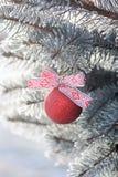 与一条丝带的发光的圣诞节球在一棵积雪的树 抽象空白背景圣诞节黑暗的装饰设计模式红色的星形 免版税图库摄影