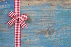 与一条丝带的红色/白色checkerd弓在木蓝色背景f 免版税库存图片