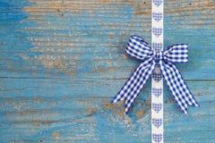 与一条丝带的蓝色checkerd弓在ch的木蓝色背景 库存照片