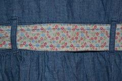 与一条五颜六色的传送带的牛仔布背景 库存图片