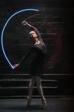 与一条五颜六色的体操丝带的年轻跳芭蕾舞者训练 免版税图库摄影