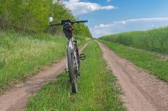 与一条土路的春天风景在一辆农业领域和自行车旁边 库存图片