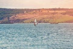 与一条孤立白色风船的美好的海景在距离 晴朗的日 覆盖积云天空 免版税库存图片