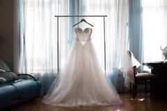 与一条宽下摆女裙的完善的婚礼礼服在挂衣架 库存图片