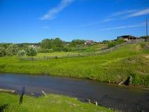 与一条小河的农村风景 免版税库存图片