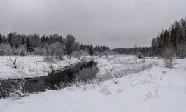与一条小河的冬天风景 免版税库存照片