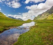 与一条小河的山风景在绿色山谷 免版税库存图片