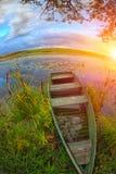 与一条小船的一个美丽如画的风景在湖的芦苇太阳的 免版税库存照片