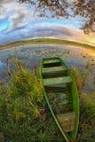 与一条小船的一个美丽如画的风景在湖的芦苇 库存图片