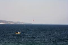 与一条小船的帆伞运动在海 库存照片