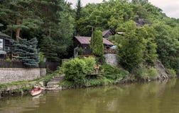 与一条小船的村庄在河岸 免版税库存图片