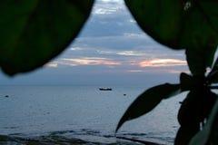 与一条小船的浪漫日落在海洋 免版税库存照片