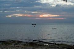 与一条小船的浪漫日落在海洋 库存照片