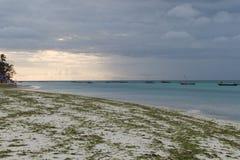 与一条小船的浪漫日落在海洋 免版税图库摄影