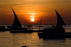与一条小船的浪漫日落在海洋 免版税库存图片