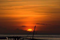 与一条小船的浪漫日落在海洋 图库摄影