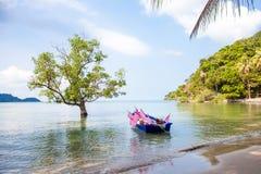 与一条小船的热带海滩在水中 库存图片