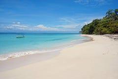 与一条小船的白色沙子海滩在系泊浮筒 库存照片
