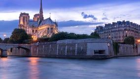 与一条小船的紫色多云天空晚上在与Notre Dame塔背景垂直位置的塞纳河银行 免版税库存图片