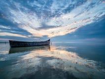 与一条小船的美好的早晨风景在日出的湖 免版税库存照片