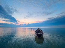 与一条小船的美好的早晨风景在日出的湖 免版税库存图片