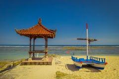 与一条小船的美好的晴天在黄沙在Pantai pandawa海滩,在巴厘岛,印度尼西亚 免版税库存图片