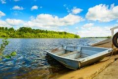 与一条小船的Minimalistic水平的风景在镇静河、绿色森林和多云天空 它完善的` s 库存图片