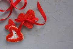与一条弓和丝带的三个心脏曲奇饼在灰色具体背景 情人节和爱概念 免版税图库摄影