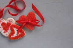 与一条弓和丝带的红色心脏曲奇饼在灰色具体背景 红色上升了 免版税库存照片